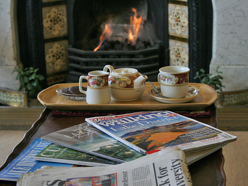 A much loved antique coffee table with a pot of tea and biscuits set before a cosy fire in our lounge..