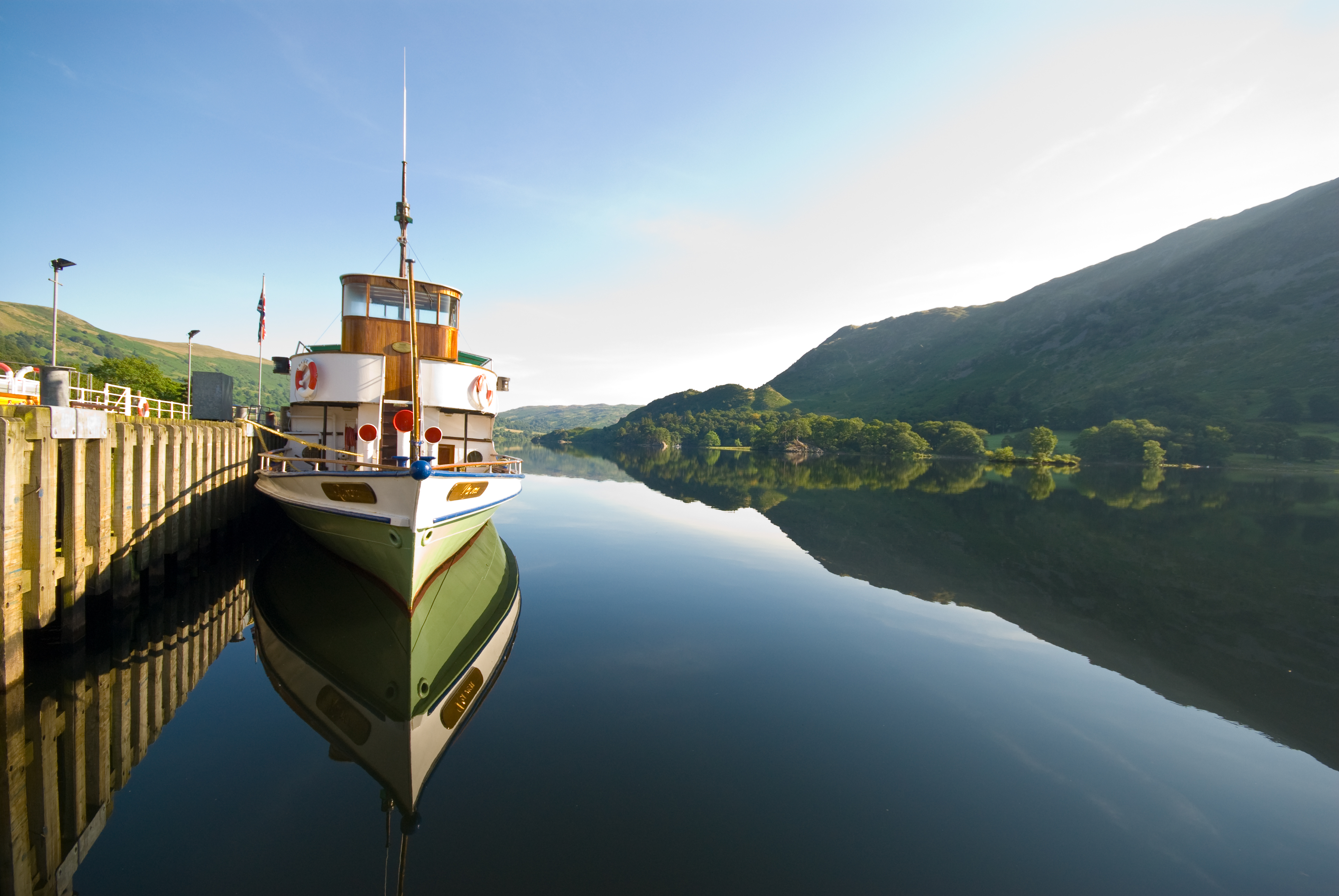 A steamer awaits passengers by the pier at Glenridding, perfectly reflected in the very still waters of tranquil Ullswater. (Photo courtesy of www.cumbriaphoto.co.uk.)