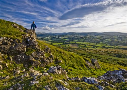 A climber looks out over the Lowther Valley, where greyish white clouds part to reveal blue skies. (Photo by Dave Willis, courtesy of www.cumbriaphoto.co.uk.)
