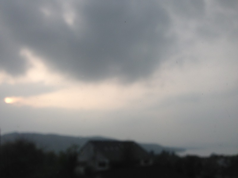 The evening sun is a bright ball of light on the left side of the photo, just beginning to be obscured by evening cloud. To the right is Lake Windermere, surrounded by fells. This photo was taken from our lounge at Blenheim Lodge in Bowness on Windermere.