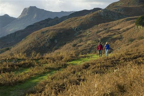 'Couple walking on a footpath at Silver Howe in the Langdale Valley with the Langdale Pikes behind.' (Photo by Tony West.)