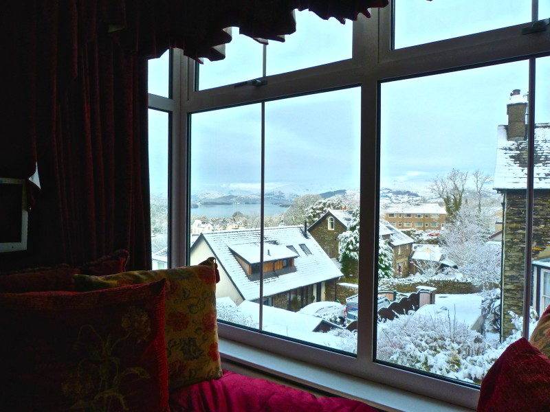 There are huge floor to ceiling bay windows in The Fairfield looking over Lake Windermere and the fells. Here is the view from the daybed in The Fairfield room when it snowed on 17 Feb 2016.