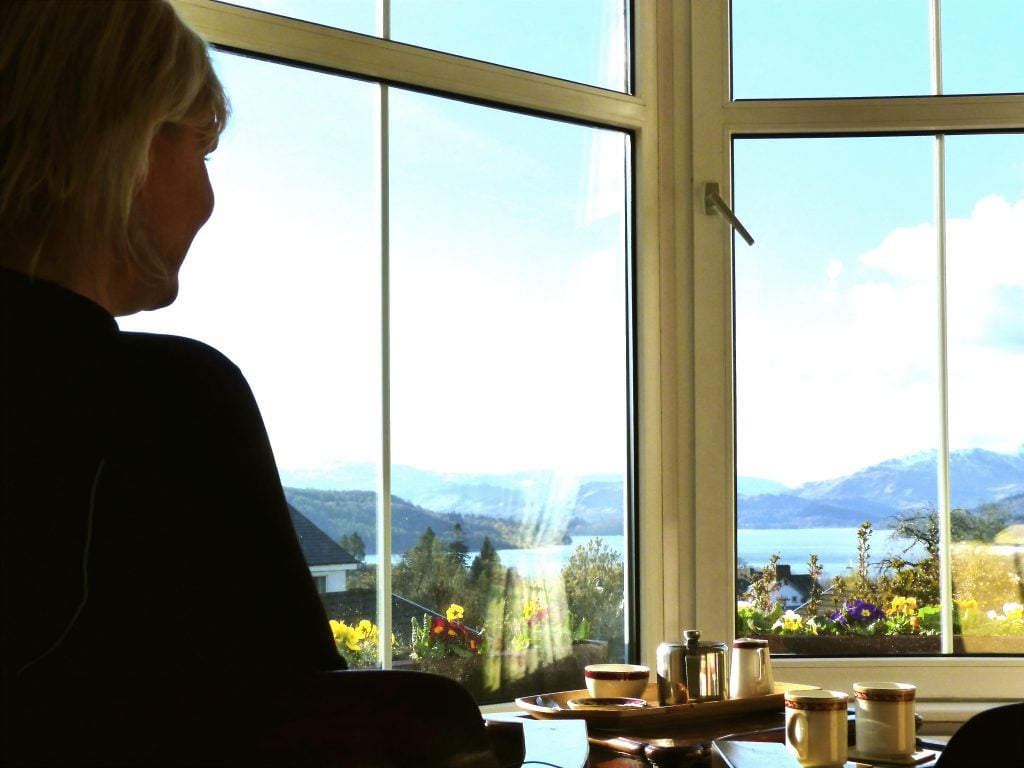 A guest relaxes with a cuppa in front of the picture window in our lounge. Those lake views are amazing!