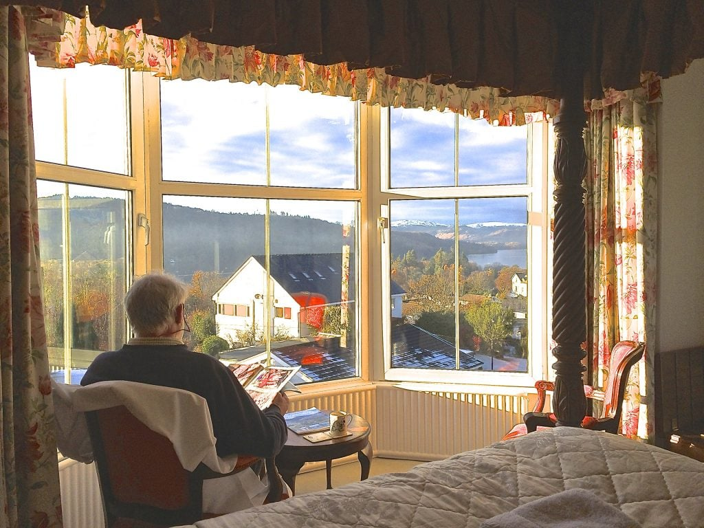 Reading the paper in front of large floor to ceiling picture bay windows in The Langdale guest room at Blenheim Lodge.