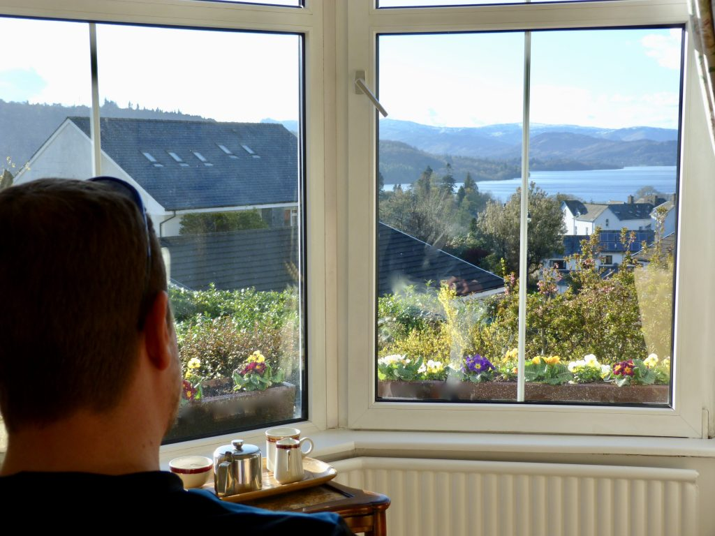 guest looks out to Lake Windermere from Blenheim Lodge's lounge
