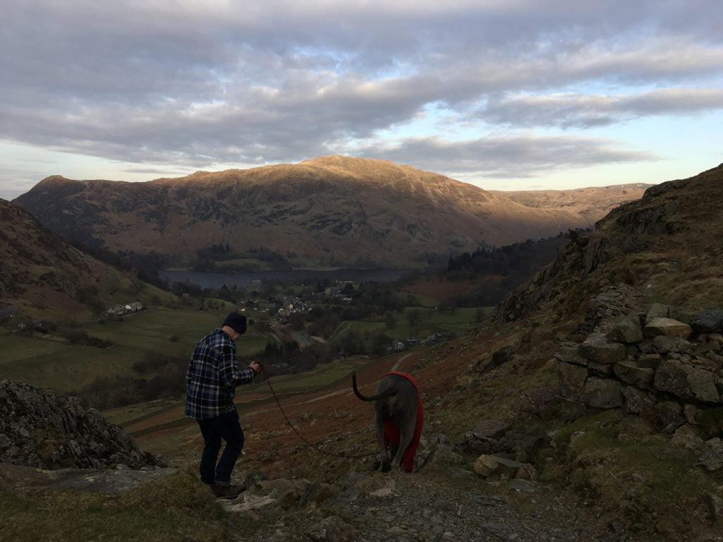 Man and dog walk down a mountain